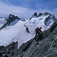 13-year old Ben Wiltsie climbs the Cain Route on Bugaboo Spire in Bugaboo Provincial Park, British Columbia, Canada.  Behind him are the Vowell Glacier, Pigeon Spire and the Howser Spire Massif.