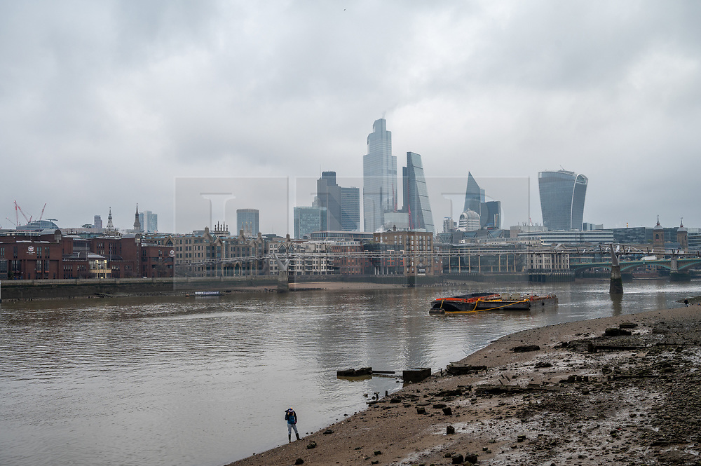 © Licensed to London News Pictures. 01/02/2021. London, UK. A woman walks on the shoreline of the River Thames al low tide. near the Millennium Bridge. London is currently in Tier-4 advising people to stay at home. Today marked the 1st anniversary of first UK Covid-19 person. Since then, over, 100,000 people have died in the UK with the Covid-19 disease. Photo credit: Ray Tang/LNP