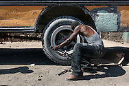 A mechanic checks bolts on a school bus in Lestère, a town where vehicules are repaired after traveling the demanding surfaces of the National Highway 1. Lestère, Haiti, January 23, 2008.