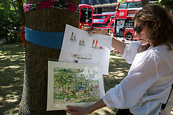 London, UK. 26th June 2018. Local resident Primavera Boman-Behram holds images of trees in Euston Square Gardens and construction workers on site as part of a protest using art against the planned felling by HS2 Ltd of mature London Plane, Red Oak, Common Lime, Common Whitebeam and Wild Service trees to make way for temporary sites for construction vehicles and a displaced taxi rank as part of preparations for the HS2 high-speed rail line. The protest, involving the capturing of images of the trees on paper using a variety of different techniques, was hosted by the artist Dan Llywelyn Hall as 'The Last Stand Against the Environmental Damage of HS2'.