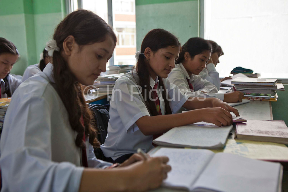 Female Nepalese pupils studying in a classroom in the Rara Hill Memorial School run by the community in the Kiretipur area of Kathmandu Valley, Nepal.  The girls are reading and writing in their exercise books.  They all wear school uniform.