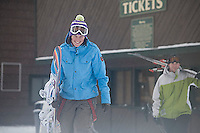 Young woman and man walking to chairlift at Kirkwood, CA.