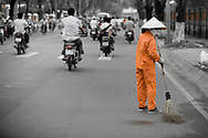 Street cleaner, Ho Chi MInh city, Vietnam.  There are roughly 4 million motorcycles and 500,000 automobiles in the city.