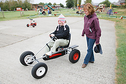 Woman with learning disability riding go-carts on visit to farm, with carer