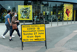 """© Licensed to London News Pictures. 27/06/2021. WATFORD, UK. A sign outside a pop-up mass vaccination clinic at Watford FC's Vicarage Road Stadium as part of the """"Grab a jab"""" campaign. The NHS is also promoting a number of walk-in clinics this weekend across the capital to try to increase the number of over 18s receiving a jab as cases of the Delta variant are reported to be on the rise..  Photo credit: Stephen Chung/LNP"""