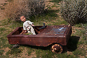 Rusty toy car with doll in Pioneer Town garden  California.