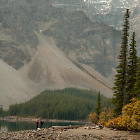 Hikers stand beside Moraine Lake in Banff National Park, Alberta, Canada. Behnind are Mounts Bowlen and Tonsa.