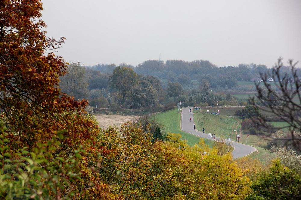 Fietsers rijden over de dijk bij de Ooijpolder.<br /> <br /> Cyclists ride on the dyke near the Ooijpolder.