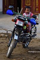 Baby sitting on a motocycle into the camera at Tongbiguan, Dehong, Yunnan, China