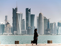 View along waterfront of Corniche towards modern office towers in Doha Qatar