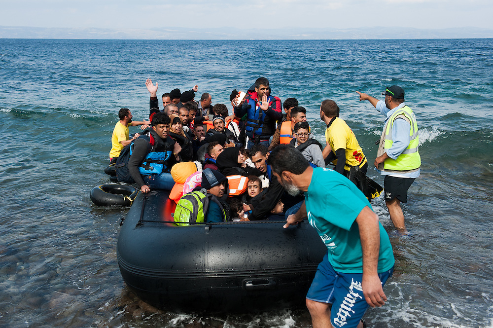 People getting off a dinghy that just landed at the beach of Skala Sykamias, Lesvos, Greece.