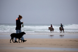 © Licensed to London News Pictures. 04/07/2020. Perranporth, UK. Emily Dunstan (C) and Tina Wallace (R) ride horses along Perranporth beach in Cornwall today, despite wet weather. Today marks a lift in COVID-19 restrictions, as pubs are allowed to open, whilst customers must still follow social distancing guidelines. Tens of thousands of tourists are due to arrive in Cornwall over this weekend, as overnight stays within England are also allowed. Photo credit : Tom Nicholson/LNP