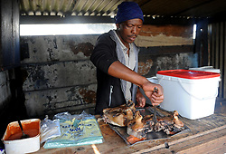 Cape Town-180906 Sinoxolo Mcetywa dishing out the Sheep head. The Sheep head also know as Smiley is very popular in the township it used to be cooked only if there was traditional cremony nowadays there are many places that clean and sell this delicacy,cooked or uncooked Sheep head cost R70 and half R35 Pictures Ayanda Ndamane/African/news/agency ANA