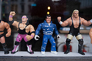 Plastic action figures of wrestling characters in the window of a bar on 5th March 2021 in London, England, United Kingdom. Some of the figures are recognisabe as from popular culture like Elvis Presley.