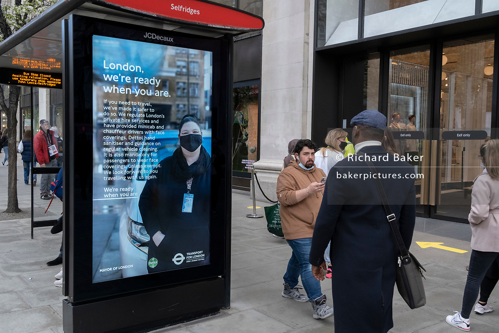 On the day that the UK government eased Covid restrictions to allow non-essential businesses such as shops, pubs, bars, gyms and hairdressers to re-open, shoppers pass the Oxford Street Primark where a digital ad's message is that London is ready for business, on 12th April 2021, in London, England.