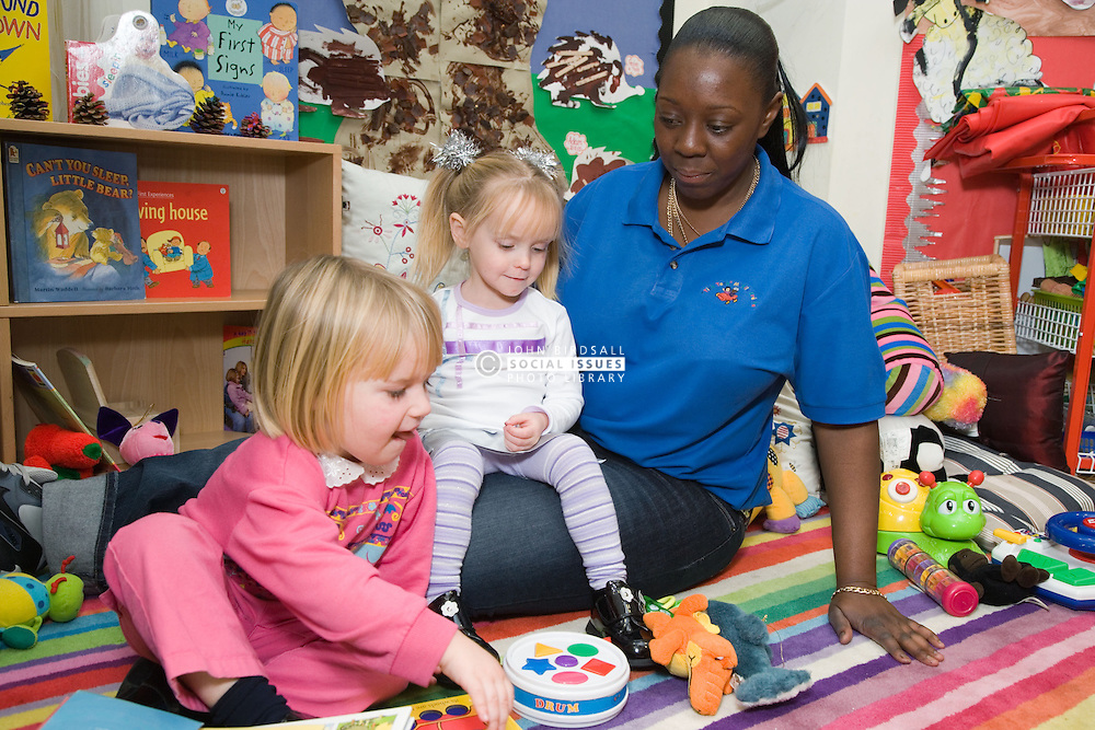 Nursery nurse; at work in mobile creche; with young girls; playing