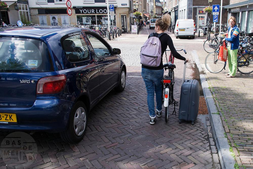 Een meisje loopt met een koffer naast de fiets door Utrecht.<br /> <br /> A girl is walking with a suitcase beside her bike.