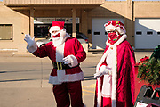 "05 DECEMBER 2020 - INDIANOLA, IOWA: STAN THOMPSON and his wife, EILEEN THOMPSON, dressed as Santa Claus and Mrs. Claus, talk to children in a car during a drive through visit with Santa Claus. This is the seventh year the Thompsons have dressed as the Clauses to entertain the children of Indianola. About 500 children visited Santa Claus and Mrs. Claus in Indianola Saturday. The town has hosted Santa on the town square for the last seven years but the COVID-19 (SARS-Cov-2) pandemic forced organizers to move the event to the parking lot of a local hardware store and do it ""drive through"" style. Iowa has one of the highest Coronavirus test rates in the United States.       PHOTO BY JACK KURTZ"