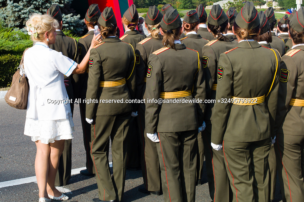 20150831 Moldova, Transnistria,Pridnestrovian Moldavian Republic (PMR) Tiraspol. Rehersal for the big parade, in the 25th  Transnistrian independance day when  they had a war separating from Moldova.female soldiers stand in the burning sun.  A woman in white holds a bottle against someones face to cool her down.
