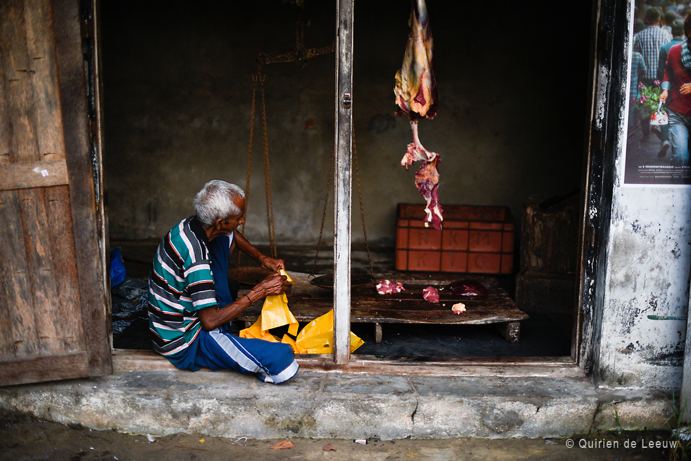 A local butcher at work is his butcher shop. Kerala province, India