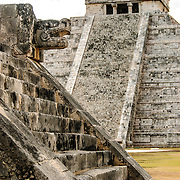 In the background at right is the Temple of Kukulkan (El Castillo) and at left in the foreground are the carved jaguar heads and steps of the Venus Platform at Chichen Itza Archeological Zone, ruins of a major Maya civilization city in the heart of Mexico's Yucatan Peninsula.