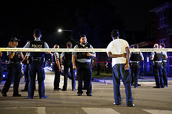 July 5, 2018 - Chicago, IL, USA - A bystander watches as officers stand on scene after shots were fired at and by the police in the Austin neighborhood early Wednesday July 4, 2018 in Chicago. Neither the suspect or officer was shot during the incident. (Credit Image: © Armando L. Sanchez/TNS via ZUMA Wire)