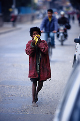 Kathmandu, 20 February 2005.  A child is sniffing glue on the street of the Capital