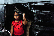Young girl sheltering in a rickshaw looks out at monsoon rains, Goa, India