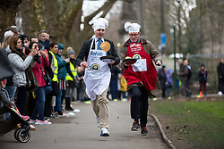 © Licensed to London News Pictures. 13/02/2018. London, UK. Matt Warman MP and James Landale race in the Rehab Parliamentary Pancake Race 2018 in Victoria Tower Gardens. The Parliament Team - made up of MPs, Lords and Ladies - race in a relay against the Media Team - made up of reporters and presenters - whilst continuously flipping pancakes to celebrate Shrove Tuesday, also known as Pancake Day. Photo credit : Tom Nicholson/LNP