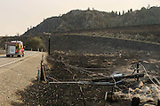 A fire truck passes by a burned down utility pole along Conconully Road, about 10 miles south of the town, Friday August 21, 2015.<br /> <br /> Bettina Hansen / The Seattle Times