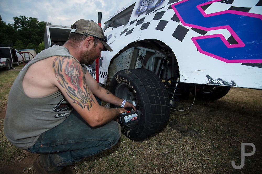 An unkown crew chief changes a rear tire on a stock car.
