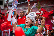 01 JULY 2011 - BANGKOK, THAILAND:  A woman wearing a hat showing a likeness of Yingluck Shinawatra, the Pheua Thai candidate for Prime Minister, cheers for Yingluck during a Pheua Thai rally in Bangkok Friday. Thailand's divisive election campaign drew to a close Friday in Bangkok. Most of the parties had large rallies in an effort to sway last minute undecided voters. Pheua Thai, the party of ousted Prime Minister Thaksin Shinawatra held a massive rally in Rajamakala Stadium (also called Ramkamhaeng Stadium) to close out their campaign. A monsoon thunderstorm didn't keep people away from the event. Most Thai public opinion polls show Pheua Thai with a healthy lead over their arch rivals (and incumbent party in power) the Democrats. Thaksin's youngest sister, Yingluck Shinawatra, is running for Prime Minister under the Pheua Thai banner. If elected, she will be Thailand's first female Prime Minister.      PHOTO BY JACK KURTZ