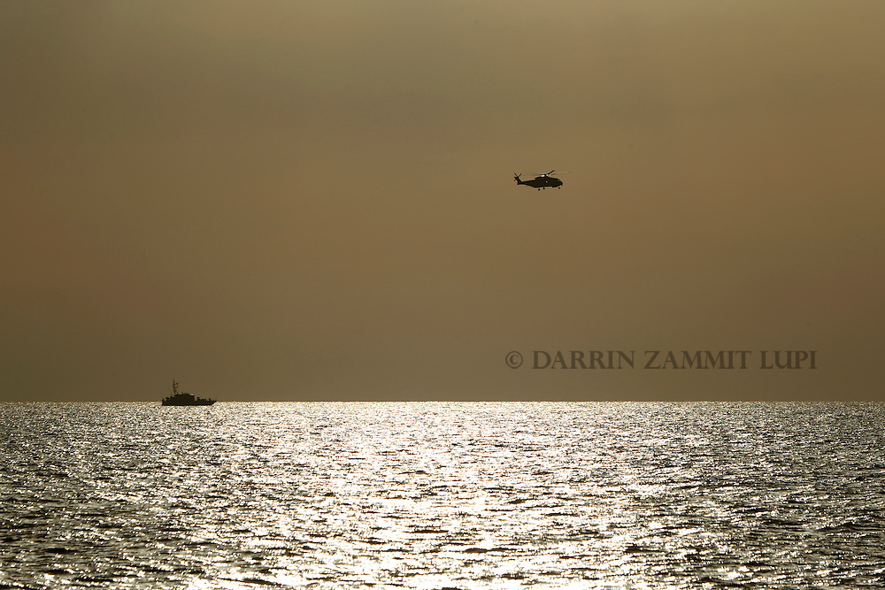 An Italian Navy helicopter and Coast Guard vessel take part in a search for missing migrants after their boat capsized off the coast of Libya August 5, 2015.  A boat packed with up to 700 African migrants capsized in the Mediterranean Sea off the coast of Libya on Wednesday and many were feared dead, officials and aid agencies said. <br /> REUTERS/Darrin Zammit Lupi <br /> MALTA OUT. NO COMMERCIAL OR EDITORIAL SALES IN MALTA