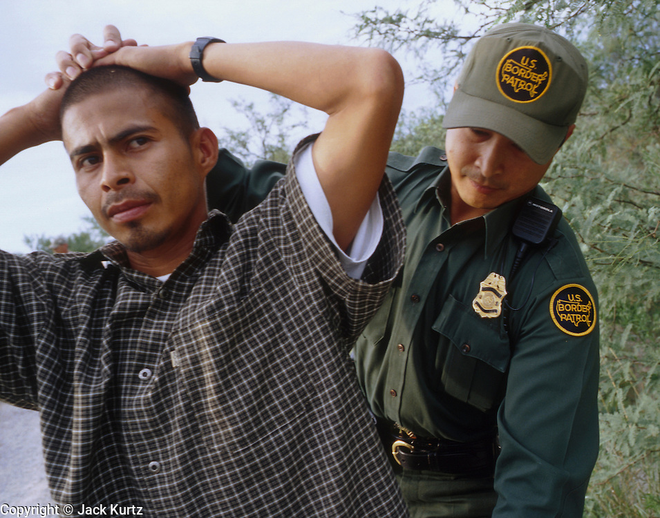 27 JULY 2001 - NACO, ARIZONA, USA: Butch Gamboa, a 5 1/2 year veteran of the US Border Patrol, searches Pablo Cesar Marquez-Perez, an undocumented immigrant from Mexico, after he apprehended him trying to enter the US illegally near Naco, AZ, July 27, 2001. Undocumented immigration from Mexico through southeastern Arizona has gone down by more than 40 percent in 2001 because of increased Border Patrol activity along the Arizona/Mexico border. .PHOTO BY JACK KURTZ