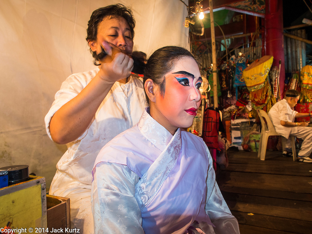 23 SEPTEMBER 2014 - BANGKOK, THAILAND: 23 SEPTEMBER 2014 - BANGKOK, THAILAND:  A performer at the Chinese opera gets help putting on her makeup on the first day of the Vegetarian Festival at the Chit Sia Ma Chinese shrine in Bangkok. The Vegetarian Festival is celebrated throughout Thailand. It is the Thai version of the The Nine Emperor Gods Festival, a nine-day Taoist celebration beginning on the eve of 9th lunar month of the Chinese calendar. During a period of nine days, those who are participating in the festival dress all in white and abstain from eating meat, poultry, seafood, and dairy products. Vendors and proprietors of restaurants indicate that vegetarian food is for sale by putting a yellow flag out with Thai characters for meatless written on it in red.    PHOTO BY JACK KURTZ    PHOTO BY JACK KURTZ