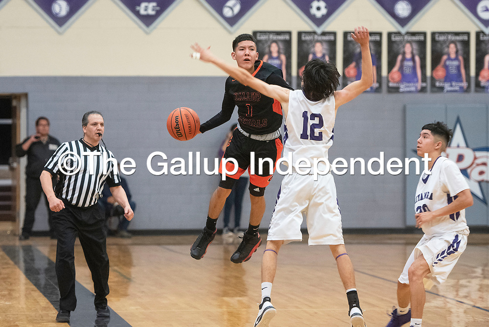Gallup Bengal Quentin Richards (1) jumps to save a ball heading out of bounds as Miyamura Patriot Lance Evans (12) defends Friday night at Miyamura High School in Gallup. Gallup took the win 76-46.