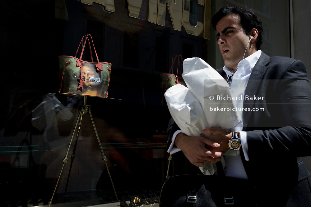 A man carrying wrapped products passes the luxury shop window of Louis Vuitton featuring their exclusive range of bags with the face of Leonardo da Vinci's Mona Lisa - a collaboration with the artist Jeff Koons and part of work entitled The Masters Collection, on 5th July 2017, on New Bond Street, in London England.