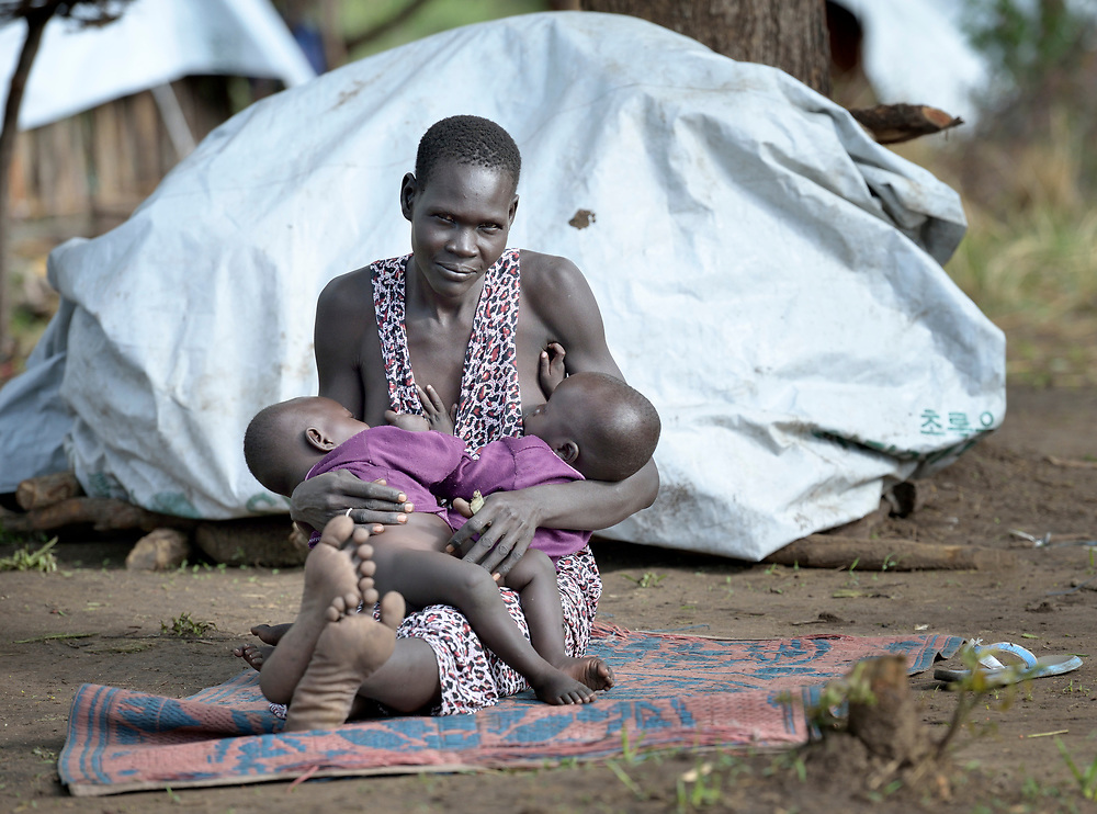 Nor Madit breast feeds her twin children in a camp for displaced people in Melijo, South Sudan, near that country's border with Uganda. Families here fled fighting around Bor, in Jonglei State, in December 2013, but have not been warmly welcomed to this region of Eastern Equatoria State, where two earlier waves of displaced people in the 1980s and 1990s have left relations tense between the newcomers, who are Dinka, and the largely Ma'adi residents around the city of Nimule. The ACT Alliance is helping the displaced families and the host communities affected by their presence, and is supporting efforts to reconcile the two groups.
