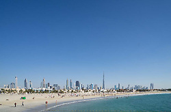 Jumeira Open Beach with tourists and skyline of skyscrapers in Dubai United Arab Emirates