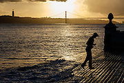 One man jumps playing with the waves of Tagus river at Cais das Colunas in Lisbon