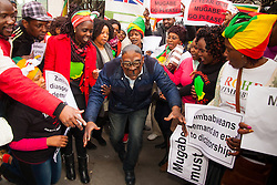 Lodon, February 21st 2015. Dozens of exiled Zimbabweans gather outside their embassy in London proclaiming Mugabe's last birthday in office. Singing and dancing as they have done every Saturday since 2002, the group spoke with passersby and added yet more names to their petition. PICTURED: