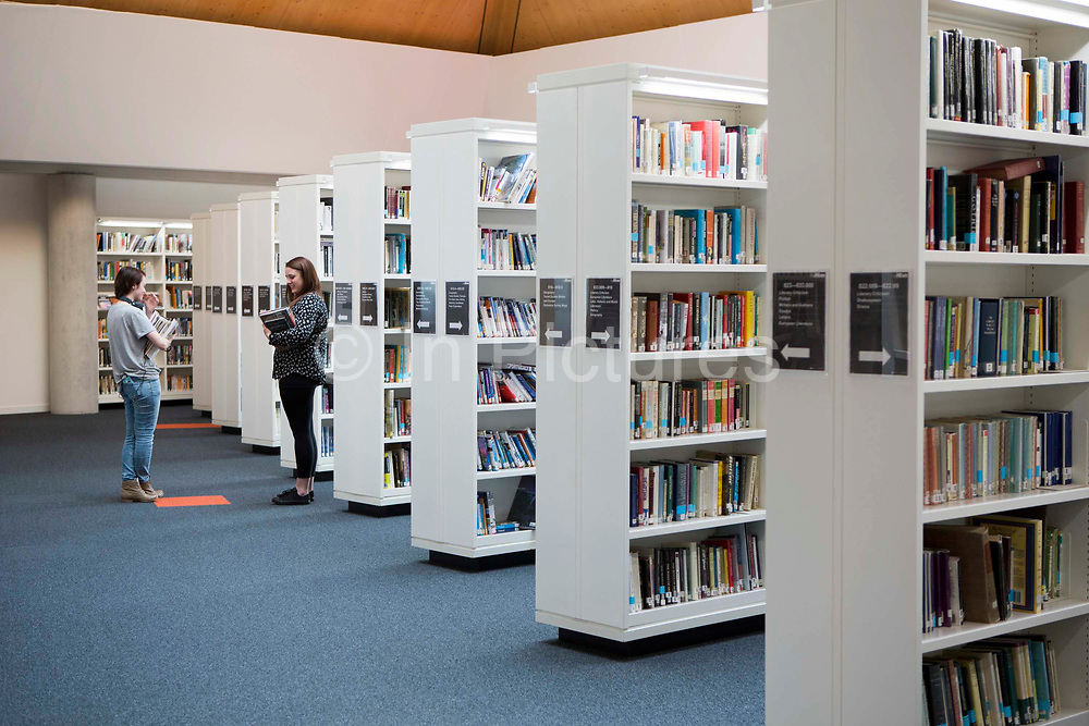 Students stand chatting inside the library of the Hive in Worcester, UK. The first fully integrated university and public library in the UK. It houses the county archives and archaeology service, the local history centre and is also a local authority hub. The building is low energy.