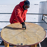 Kael Hanson pointing to where the new strings of DOMs (digital optical modules) will be installed at IceCube over the next few years. Each string requires a hole drilled into the ice over 1 kilometer deep, into which the strings of DOMs are hung.