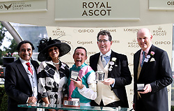 Jockey Frankie Dettori and trainer John Gosden are presented with the trophy by Meera Syal and Sanjeev Bhaskar after winning the Wolferton Stakes with Monarchs Glen during day one of Royal Ascot at Ascot Racecourse.