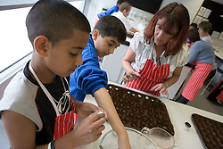 Technician helping students to make sweets in introductory Food Studies lesson during their induction day,