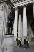 Two officers on horses with the mounted City Police, patrol beneath the war memorial and columns of Conhill Exchange in the City of London, the capitals financial district, on 14th March 2018, in London England.
