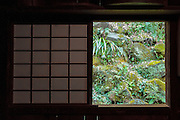 The paper door of a house in Sankei en  Garden showing a lush green garden outside. Naka Ward, Yokohama, Kanagawa, Japan. Friday February 26th 2016 A traditional Japanese style garden that opened in 1906 and house a number of culturally and historically important structures collected from all over Japan.