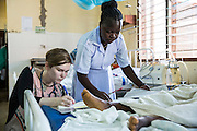 Dr Siobhan Neville and a nurse update patient notes on the Intensive care ward during the daily rounds.  St Walburg's Hospital, Nyangao. Lindi Region, Tanzania.