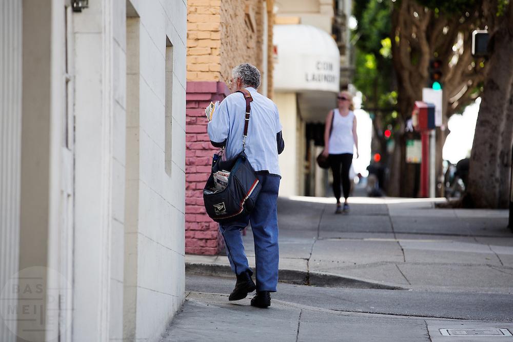 Een postbode doet zijn ronde in San Francisco. De Amerikaanse stad San Francisco aan de westkust is een van de grootste steden in Amerika en kenmerkt zich door de steile heuvels in de stad.<br /> <br /> A postman is walking his route in San Francisco. The US city of San Francisco on the west coast is one of the largest cities in America and is characterized by the steep hills in the city.