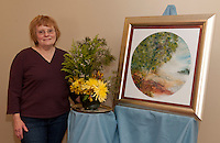 In preparation for Opechee Garden Club's Art 'n Bloom at Gilford Library Judy Riley presents her floral interpretation of her sister Haze Needham Schultze's artwork Royall's Cove.  (Karen Bobotas/for the Laconia Daily Sun)